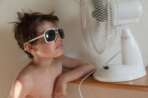 little boy in front of fan